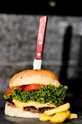 Ein Burger mit Pommes und einem Messer