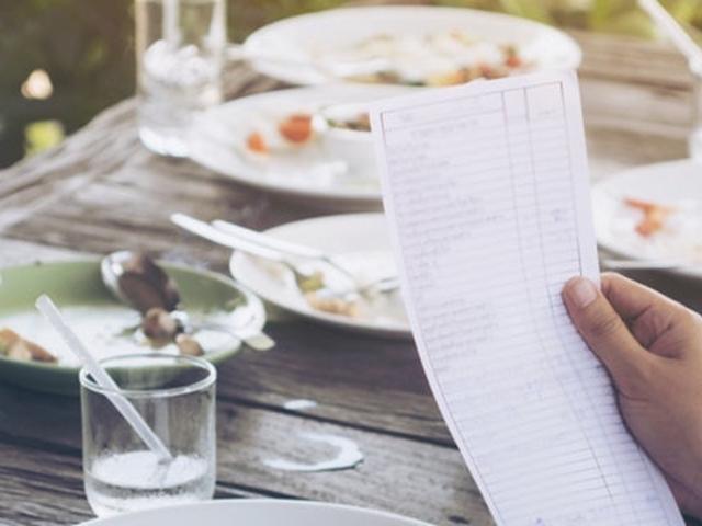 Bild von einem Tisch mit Geschirr und einer Hand mit einer Rechnung